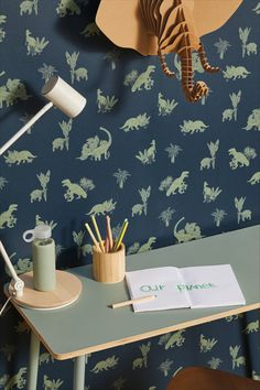 Curious dinosaurs are seen in a playful and modern design amongst luscious trees and plants; set against a plain and bold background. Navy Wallpaper, Words Wallpaper, Blue Wallpapers, Jurassic World, Pattern Matching, Our Planet, Merlin, Decoration, True Colors