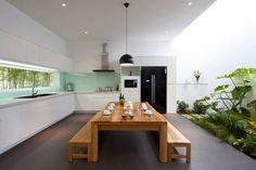 grande cuisine avec table et bancs en bois, armoires blanches et jardin exotique
