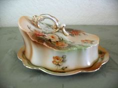 Butter Dish or Cheese Keeper Peach-colored Roses - This is another example of reproduction-type items often offered for sale as 'vintage' or 'antique,' even though they are not at all old. This covered dish decorated in shades of ivory, peach and green, with gold accents, may resemble real R.S. Prussia marked fine German dishes, but it is a fake.