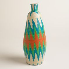 Handcrafted on the Indonesian island of Lombok, our extra large terracotta vase is wrapped in orange and green batik fabric for a splash of vibrant style. With its slim silhouette and bold pattern, it's an eye-catching display piece.