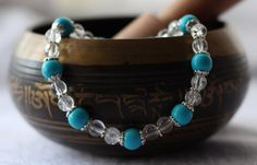 Vivid turquoise-blue magnesite beads adorned with silver bead caps. - Crackle glass beads and daisy silver spacers finish the design. - 8 Inches un-stretched (approximately). This bracelet best fits people with a medium or large frame (for reference, the wrist in the picture is a 6.5 inch - small/medium wrist). - Ships from Canada.  This cute bracelet looks flirty and dainty alone, but...