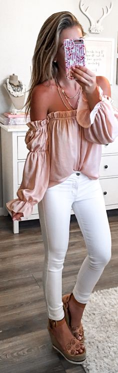 #spring #outfits woman wearing pink off-shoulder top and white fitted jeans and pair of brown leather wedges standing holding Android smartphone. Pic by @laurabeverlin