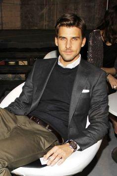 Grey jacket, dark grey sweater, white dress shirt, brown belt, dark olive trousers