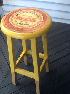 Old wooden bar stool restyled in todays fashion colours with Coca Cola advertising.
