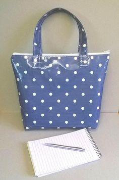 This is a lovely ladies tote bag made in oilcloth Zip closure to keep items safe inside Denim blue with white spots Two matching strong handles to wear over the forearm Long white zip Flat bottom and will stand up on its own Can be wiped clean or gently hand washed Measures approx - 12 1/2 inches x 10 inches (32 cm x 26 cm) Handles from zip to the top - 6 1/2 inches (17 cm) Will keep items dry inside or perfect to store damp clothes etc.. Perfect for carrying shopping, lunch etc.. I...
