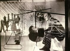 """Marcel Duchamp photographed by Mark Kauffman behind his early masterwork """"The Large Glass"""" at the Philadelphia Museum of Art."""