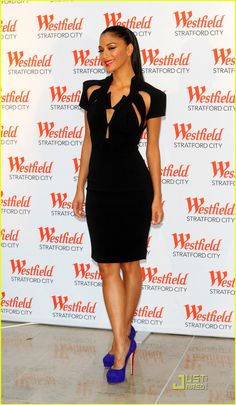 In a black cutaway shift dress and electric blue suede heels at the opening of Westfield Stratford City