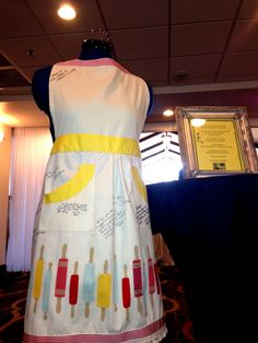 An apron acts as a guestbook for a 1960s theme bridal shower!  We just love the creativity of our hosts!