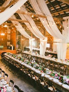 Rustic barn wedding reception space with draped white fabric decor #wedding #weddingideas #barnwedding