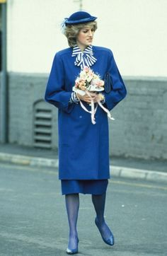 On April 5, 1984 Diana visited the Royal Doulton porcelain factory at Nile Street, Burslem, Stoke-On-Trent. Diana wore a royal-blue woollen coat by designer Bellville Sassoon, worn with a matching coloured hat, and a striped blouse in blue and white with a large bow detail, also by Belville Sassoon.