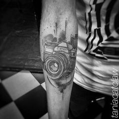 Sketch work style Canon camera tattoo on the right inner forearm.