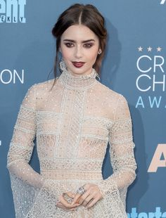 Gothic-Glam Lily Collins wearing a lacy sheer dress featuring billowy sleeves with embroidered crystals at the 22nd Annual Critics' Choice Awards at Barker Hangar in Santa Monica on December 11, 2016