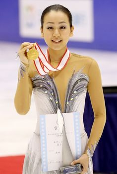 Mao Asada, smiles with her Gold medal in hand, after winning her 5th All Japan Nationals Championship.  = Makomanai Sekisui Heim Ice Arena in December 23, 2012.