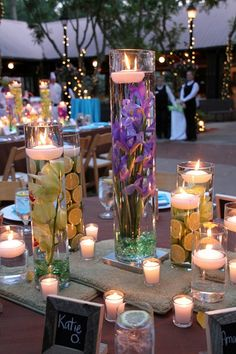 centerpieces with fresh flowers, fruits, water, glass rocks, and floating candles