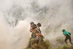 Villagers take cover during an aid-dropping operation by an Indian helicopter in Lampuk, Nepal. PHOTOGRAPH BY: DAVID RAMOS / GETTY IMAGES ASIAPAC