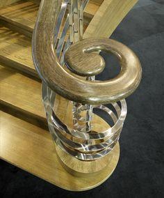 www.trabczynski.com ST650 Policzkowe schody gięte z podstopniami wykonane z barwionego dębu. Policzki z intarsją. Balustrada z szlifowanej na wysoki połysk stali szlachetnej, poręcze drewniane. Projekt – TRĄBCZYŃSKI na podstawie wzoru z pierwszej polowy XX wieku / ST650 Curved stringer stair with risers made of stained oak. Inlaid stingers. Balustrade of high-polished stainless steel, wooden handrails. Designed by TRABCZYNSKI on the basis of a design from the first half of the 20th c