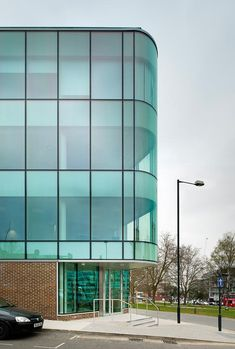 Wembley Hill Road office building with uninterupted high performance glazing, curved glass corner, and brick base.