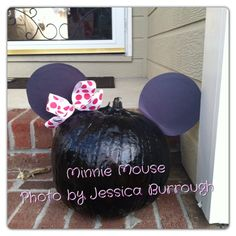 DIY Minnie Mouse pumpkin. Project less than $5. We used the cheap .97cent  black spray paint from Walmart. The pumpkin was $3.88 at Walmart. Black construction paper for the ears (we backed it with some black paper plates I already had on hand) and a used a bow I also already had. We hot glued everything on. Easy as 1.2.3
