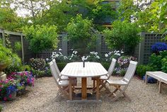 rectangle pea gravel area for dining table with planters in corners on
