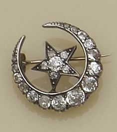A Victorian diamond set crescent and star brooch The star within closed crescent, set with graduated old-cut diamonds, gold and silver mounted, total diamond weight approximately 2ct, diameter 2.4cm