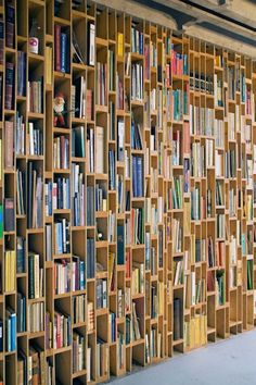 Artistic bookcase that covers the wall from floor to ceiling with various shapes and sizes intermingled for unique architectural interest | Designed by Dutch firm EventArchitectuur