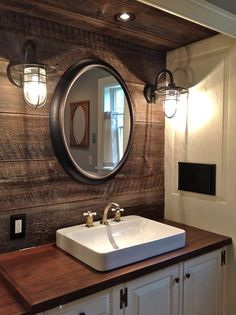 Round mirrors, industrial lighting, reclaimed barnwood, counter mounted sink, Peruvian walnut counter