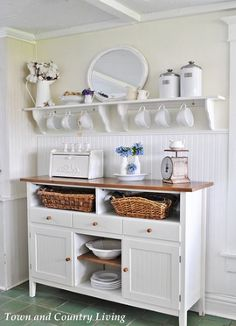 The Secret to Adding Farmhouse Style in Your Kitchen - Cups hanging from open shelves are easy to reach and ready at a moment's notice. Baskets hold linens while a breadbox keeps bread fresher longer.