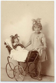 Young girl with hair bow standing next to a doll in a buggy.