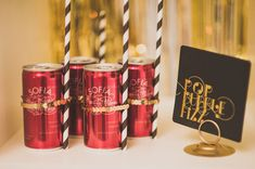 Champagne cans with straws secured to them by stretch sequins