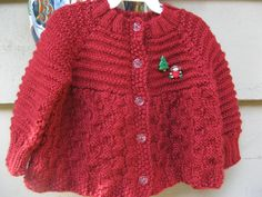 Hand knit baby girls cardigan sweater in a festive Christmas red acrylic yarn.