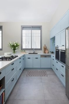 Sky Blue kitchen cabinets, white marble counter-top and concrete like floor