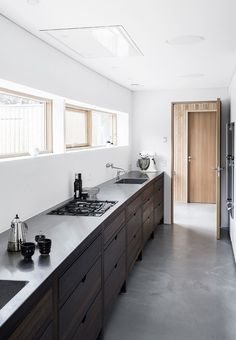 Nordic and modern kitchen with dark wooden cabinets, steel countertop and contrete flooring.