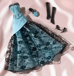French Quarter™ Barbie® Fashion. This exquisite ensemble is crafted of dusty blue taffeta set against embellishments of jet black. The strapless corset, decorated with striking lace and embroidered accents, accompanies a matching skirt with a sweep of elegant lace. Party-perfect accessories include black charmeuse gloves, a blue taffeta evening purse featuring blue embroidered details, and black high heels.