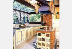 Paredes de tijolos de demolição. Os armários, pintados de amarelo, têm detalhes e puxadores no mesmo tom de azul das janelas, mesa, cadeiras e coifa. Uma ilha de tijolos com tampo de granito acomoda o fogão de bancada e gavetas para grãos