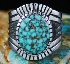 Alton Bedonie Rare Gem Grade Turquoise Mountain Spiderweb Turquoise Ring #AltonBedonie A fine gem grade natural Turquoise Mountain cabochon from Arizona is featured in this beautiful ring created by Alton Bedonie. The gem is classic sky blue with complex tight chocolate and golden-brown spiderweb matrix. Alton has set it in his signature high hand cut bezel. The shank is a work of beauty as well. Deeply stamped, etched and textured the band sits perfectly on the finger.