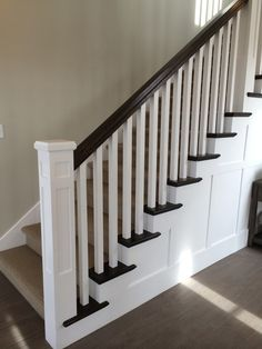 White newel post, charcoal stained handrail, white square balusters, charcoal stained tread caps, white risers