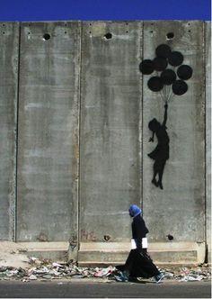 """FOTO 6: Sinds 2003 is Israël begonnen met de bouw van een muur aan de Westelijke Jordaanoever. Wat voor de ene (Israëli's) een veiligheidsmuur is tegen terrorisme, is voor de ander (Palestijnen) een apartheidsmuur die hen scheidt van familie, ziekenhuizen... De kunstenaar Banksy heeft op deze muur al heel wat werk verricht. Met zijn eenvoudige, maar krachtige tekeningen wil hij protest aantekenen tegen de Israëlische overheid """"die van Palestina de grootste buitengevangenis van de wereld…"""