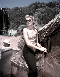 "MOGAMBO (1953) - Grace Kelly on horseback on the set of the movie ""Mogambo"" - Directed by John Ford - MGM - Publcity Still."