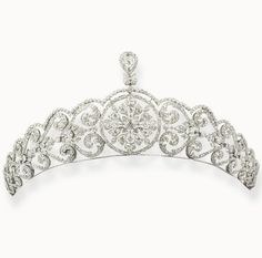 A delicate diamond belle epoque tiara, circa 1900. Featuring a circular central folate motif, topped with a pear-shaped diamond, flanked by twelve sets of foliate scrolls.