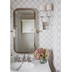Gray powder room features walls clad in white and gray geometric wallpaper lined with a curved metal mirror illuminated by a TT Double Wall Lights over a washstand with a white marble top seamlessly transitioning to a white marble sink. Powder Room Wallpaper, Of Wallpaper, Metallic Wallpaper, Half Bathroom Wallpaper, Cottage Wallpaper, Wallpaper Patterns, Geometric Wallpaper, Wallpaper Ideas, Home Luxury