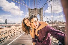 Couple taking selfie on Brooklyn Bridge - Beautiful couple taking selfie on Brooklyn Bridge, New York - Tourists having fun and photographing NY landmarks