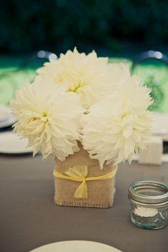 Gorgeous white flowers in vessal wrapped with burlap and yellow ribbon