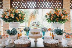 Decoração rústica em tons apastelados de laranja, azul e rosa. As bases em madeira que sustentaram os docinhos deram um toque ainda mais natural, enquanto que os corações coloridos de feltro deram um toque alegre à mesa.