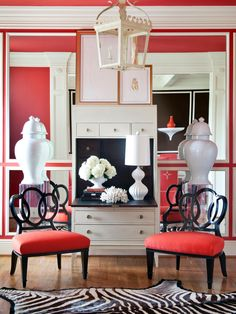 Polished with tons of character and fun, this sitting room offers a unique style. Red walls with mirror accents set the stage for this creative space. The color story is spread to the floor by red and black chairs that accompany a zebra print rug. Large white vases flank a versatile dresser that provides storage and charm, making this room perfect for just about anything.