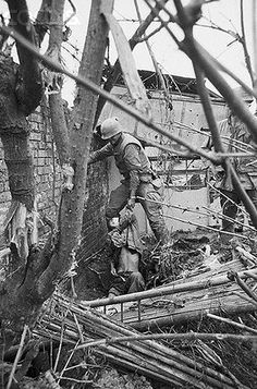 19 Feb 1968, Hue, South Vietnam --- Hue, South Vietnam: At left a U.S. Marine spots a Viet Cong lying in a hole at the base of the citadel wall during assault 2/19. The Marine hauls the wounded captive out of his pit at right. Under siege for almost a month, the citadel fell to Allied forces. --- Image by © Bettmann/CORBIS