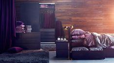紫を基調にしたベッドルームの家具の画像。木製ベッドとライラックの寝具、床にはダークグレーのラグ、ダークカラーの木製ワードローブ、チェスト、ダークパープルのカーテン。