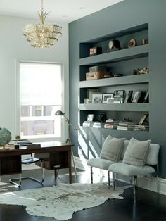 Built-in shelves with deep finished facing.  Wonder if rope lights could be hidden under shelves to light the shelf below.  Love the two shades of gray-green on the walls with the globe and all the white.