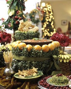 Beautiful Holiday Table Using Food as Serving RIsers.     Using string, attach boxwood sprigs to 2 or 3 layers of green styrofoam rings. Add grosgrain ribbon if desired. Stud top with tangerines or key limes using floral picks. Top with serving plate.