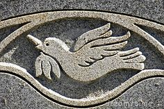 Close up of a peace dove engraving on a cemetary headstone.
