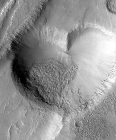 """In 1999, the Mars Global Surveyor snapped this photograph of a """"Valentine"""" from the Red Planet. The """"heart"""" is actually a pit formed by a collapse within a graben, which is a geological term for a straight-walled trough which forms along fault lines. The heart-shaped pit is 1.4 miles (2.3 kilometers) across at its widest point, and sits on the slopes of the Alba Patera volcano."""